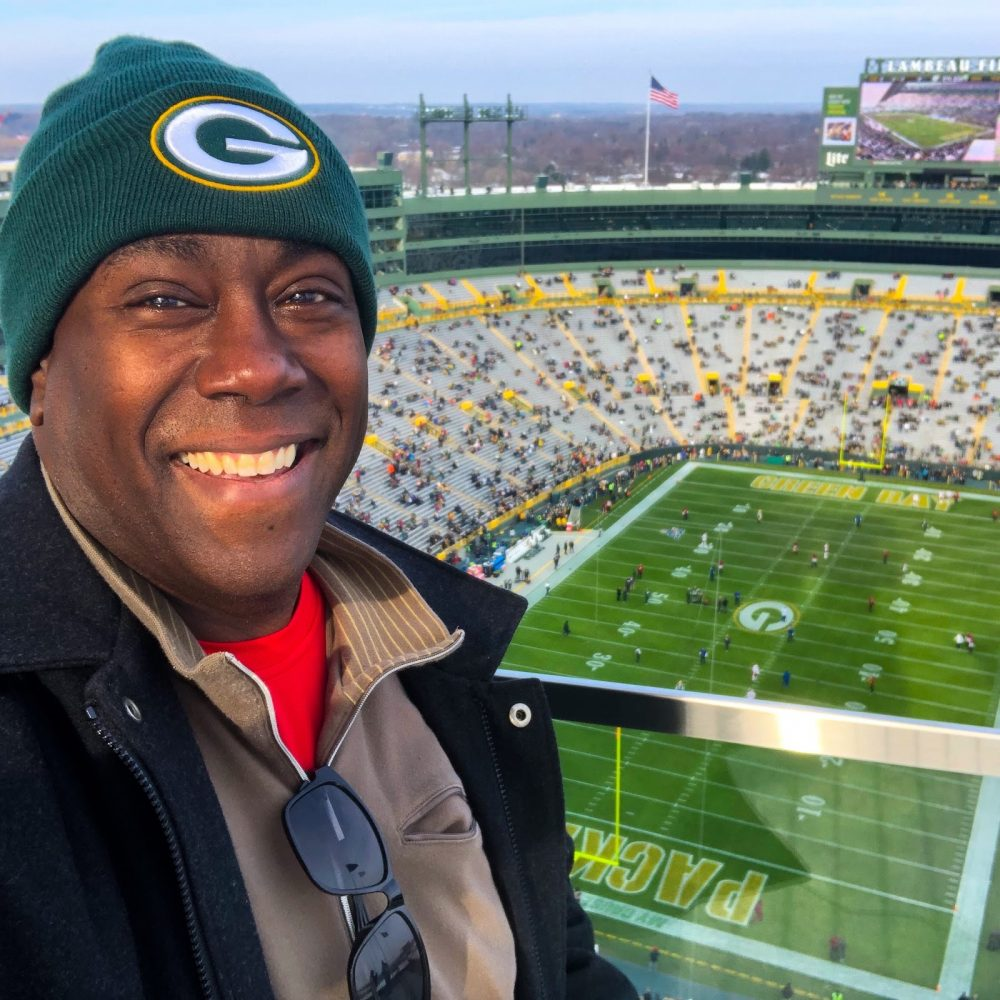 RV Jedeye smiles from an upper deck at Lambeau Field, overlooking the stadium bowl